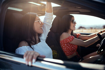 Fototapeta Pretty young women singing while driving a car on road trip on beautiful summer day. obraz