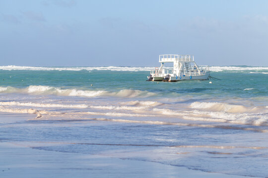 Coastal Caribbean landscape with white pleasure motorboat