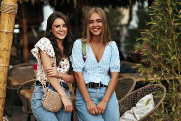 Happy brunette curly and blonde tanned women in floral blouses and stylish jeans smile sincerely,...