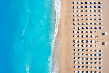 Fototapeta Top view of a beach with symmetrical sunbeds and parasols next to turquoise sea as seen in Greece obraz