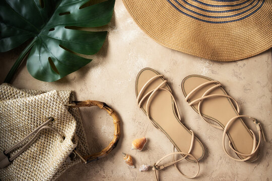 Top view of monstera palm leaf, luxury sandals, raffia bag, straw  hat and seashells on sand background. Concept for  summer times and vacation.
