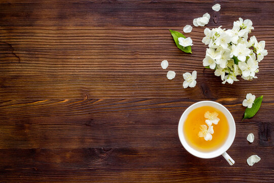 Cup of jasmine herbal tea with white flowers. Top view