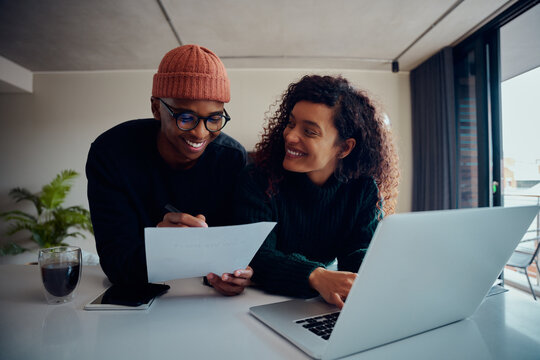 Close up of mixed race couple using laptop for online banking. Happy African American couple smiling and looking at each other while working together at home. High quality photo