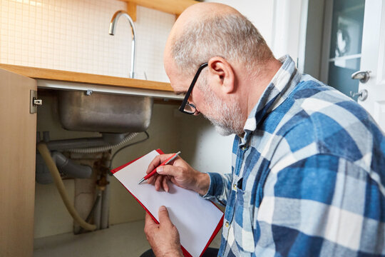 Handyman with clipboard writes an invoice