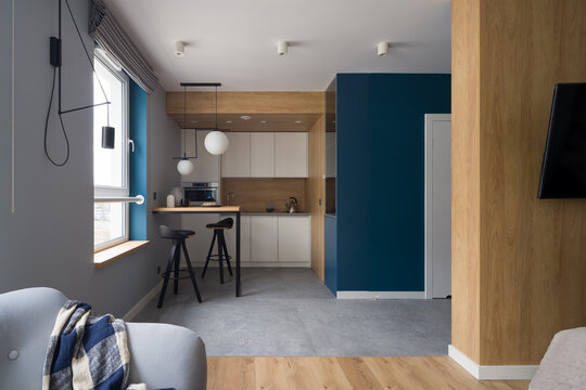 Modern kitchen open to room with cozy armchair