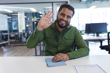 Portrait of mixed race male creative worker sitting at desk looking at camera