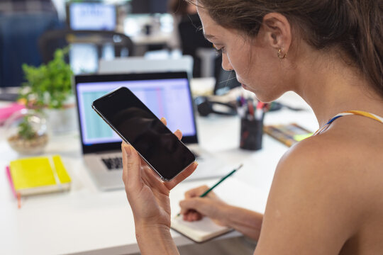 Caucasian female creative worker sitting at desk using smartphone taking notes