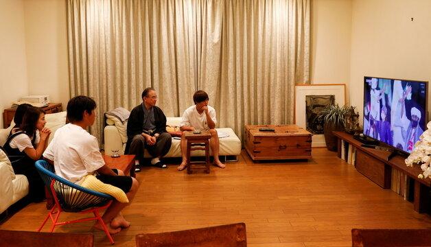 Masatsugu Kobori, Hideko Kobori, and their children Masataka, Masayasu and Noriko, watch the Tokyo 2020 Olympics Opening Ceremony on TV in Tokyo