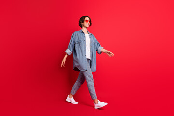 Full length body size photo girl wearing sunglass walking isolated vibrant red color background Wall mural