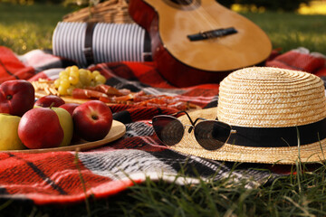 Fototapeta Straw hat, glasses and different snacks for summer picnic on plaid outdoors obraz
