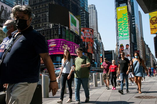 People wear masks around Times Square, as cases of the infectious coronavirus Delta variant continue to rise in New York City, New York