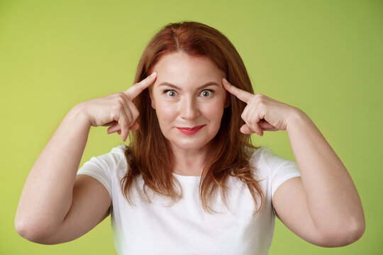 Woman playfully staring funny control your mind. Silly redhead middle-aged female touch temples popping eyes smiling delighted read thoughts trying guess intrigued what thinking green background