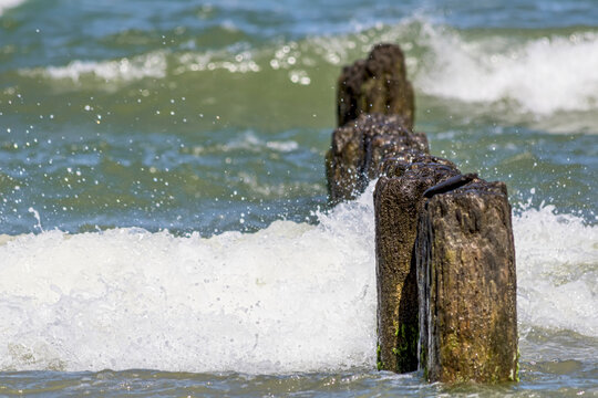 Landscapes of Poland. Breakwater  at Baltic sea. Wavy water.