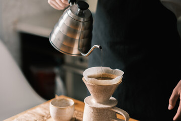Brewing pourover coffee in the kitchen, pouring hot water on the