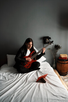 A young boy is learning to play the bass guitar in his room.
