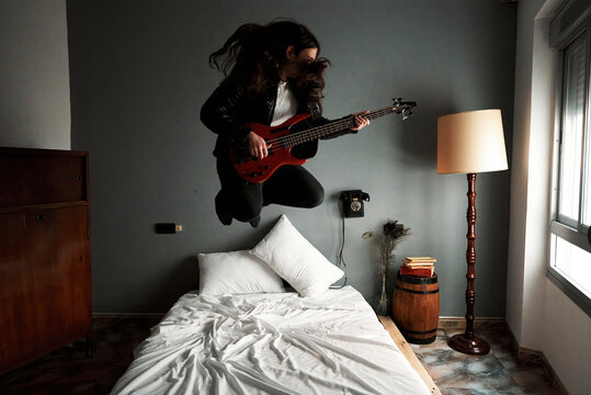 A young man with long hair jumping bed while playing the bass guitar