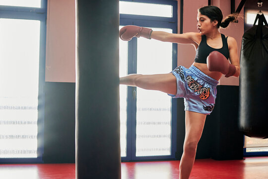 Woman trains with a punching bag in a Muay Thai gym
