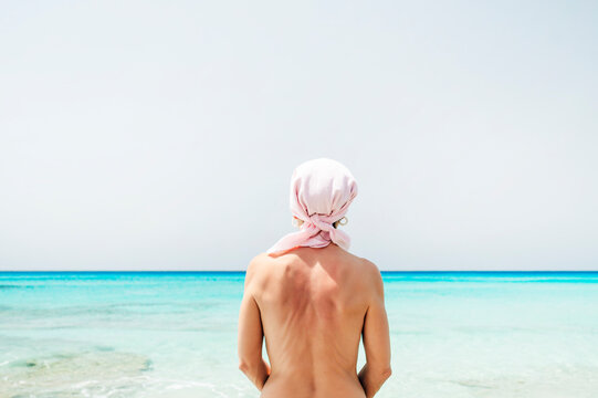 Naked woman with pink scarf on the beach, has cancer