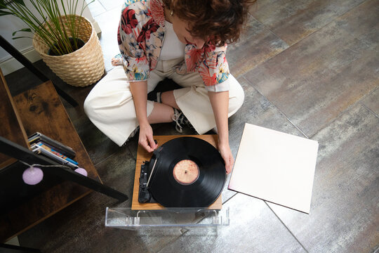 Young woman playing a vinyl record on a turntable at home