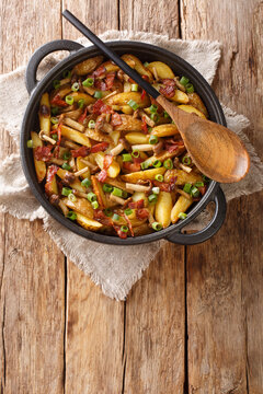 Fried potatoes with bacon and honey fungus mushrooms close-up in a frying pan on the wood background. Vertical top view from above
