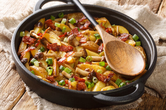 Hot rustic fried potatoes with green onions, mushrooms and bacon close-up in a frying pan on a wooden background. horizontal