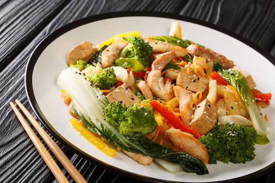 Traditional Stir fry of chicken, tofu and seasonal vegetables close-up in a plate on a black wooden background. horizontal