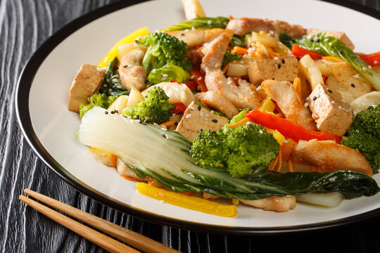 Stir fried of chicken, tofu, bell peppers, carrots, broccoli and bok choy close-up in a plate on the table. horizontal