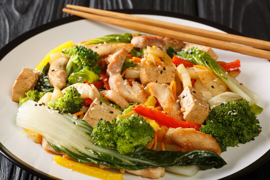 Tasty Stir fry mix of vegetables, chicken and tofu close-up in a plate on the table. Horizontal