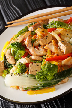 Stir fry vegetables, chicken and tofu close-up in a plate on the table. Vertical
