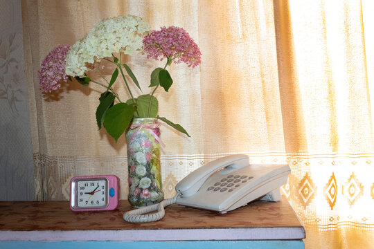 There is a wired telephone, an alarm clock and a bouquet of hydrangeas on the bedside table.