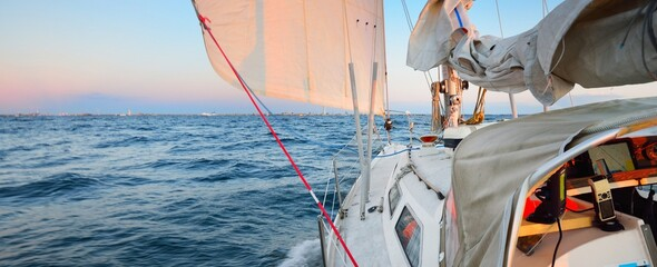 Obraz White yacht sailing in the North sea after the storm. Norway. View from the deck to the bow, mast sails. Clear blue sky, soft golden sunset light. Transportation, cruise, recreation, regatta, sport - fototapety do salonu