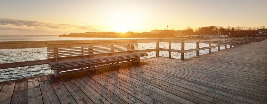 An empty wooden pier, bench close-up. People are staying home because of travel ban and coronavirus (COVID-19) outbreak. Closed ferry connection. Ystad, Sweden quarantine zone