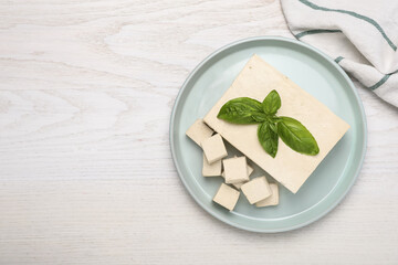 Fototapeta Delicious tofu with basil on white wooden table, top view. Space for text obraz