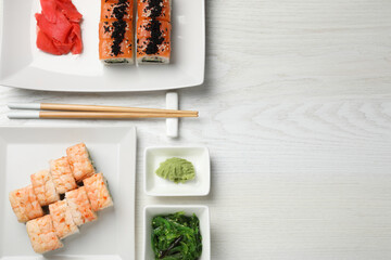 Fototapeta Delicious sushi rolls served on white wooden table, flat lay. Space for text obraz