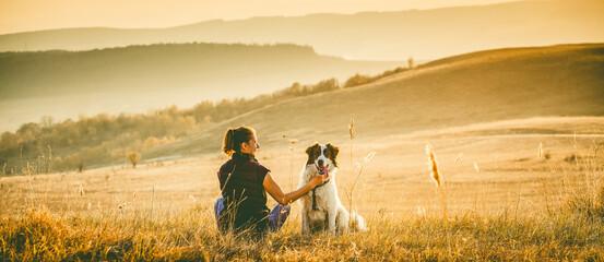 Fototapeta woman with dog relaxing in autumn landscape obraz