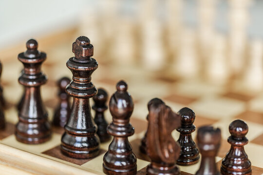 Wooden chess pieces set up on board game indoors