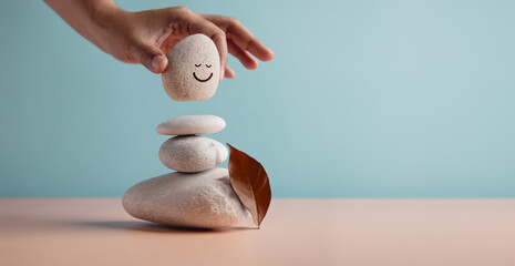 Obraz Enjoying Life Concept. Harmony and Positive Mind. Hand Setting Natural Pebble Stone with Smiling Face Cartoon to Balance on Beach Sand. Balancing Body, Mind, Soul and Spirit. Mental Health Practice - fototapety do salonu