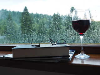 Fototapeta Kieliszek czerwonego wina i książka na tle okna obraz