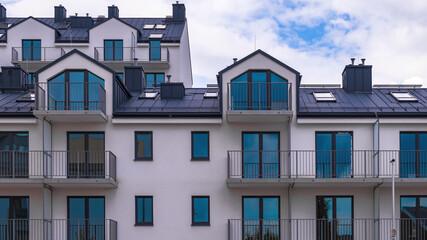 Niebieskie okna w białym budynku mieszkalnym ze spadzistym dachem z chmurami w tle