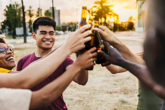 Multiracial friends celebrating and toasting beers at beach party - Group of happy people having fun together while hanging out with drinks in summer holidays with back sunlight - Focus on asian guy