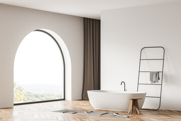 Arch window in the white bathroom space with bathtub