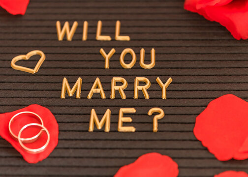 """Closeup of a """"will you marry me? text written on a black board for a proposal"""