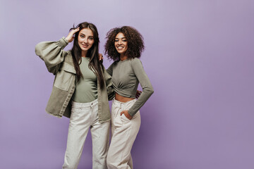 Charming curly haired woman in olive top and white trousers smiling and hugging with stylish girl...