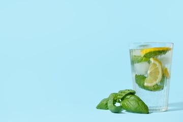 Glass of tasty lemonade with basil on background
