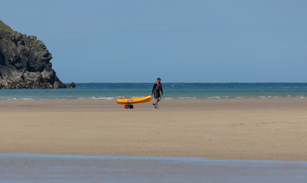 Man holding a yellow surfboard by the beach on a summer day