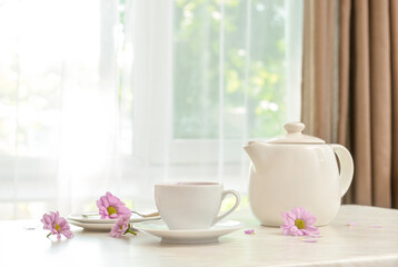 Fototapeta Cup of floral tea, teapot and flowers on table in room obraz