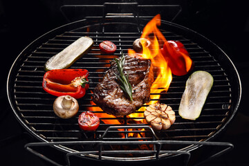 Fototapeta Barbecue grill with steak and vegetables on dark background obraz