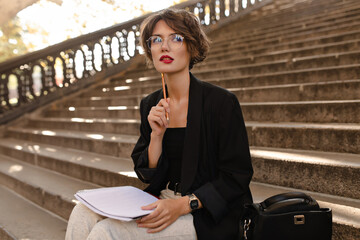 Fototapeta Pensive girl with red lips and curly hair in black jacket sitting on stairs outdoors. Brunette lady posing with notebook outside.. obraz