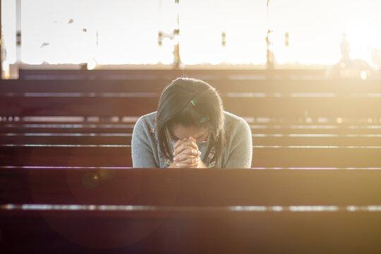 Asian woman in Thailand sitting in a church praying