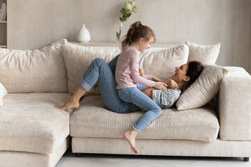 Fototapeta Small ethnic girl child and excited young Latino mom relax on couch in living room feel playful on weekend together. Overjoyed Hispanic mother and little daughter have fun play and tickle at home. obraz